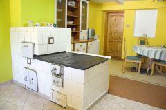 Prostorná kuchyň s kachlovými kamny a jídelním koutem